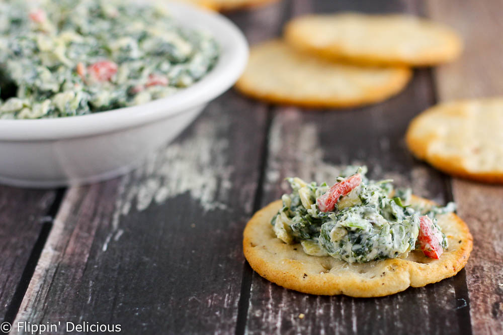 Creamy gluten-free skinny spinach artichoke dip made with greek yogurt. Packed full of veggies and protein, and less guilt when you eat it all.